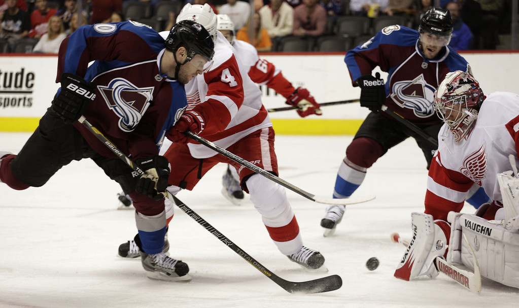 . Colorado Avalanche defenseman Tyson Barrie (41) shoots on Detroit Red Wings goalie Jimmy Howard, right, and defenseman Jakub Kindl (4) as Avalanche right wing David Van der Gulik (14) moves into the play in the first period of an NHL hockey game on Friday, April 5, 2013, in Denver. (AP Photo/Joe Mahoney)