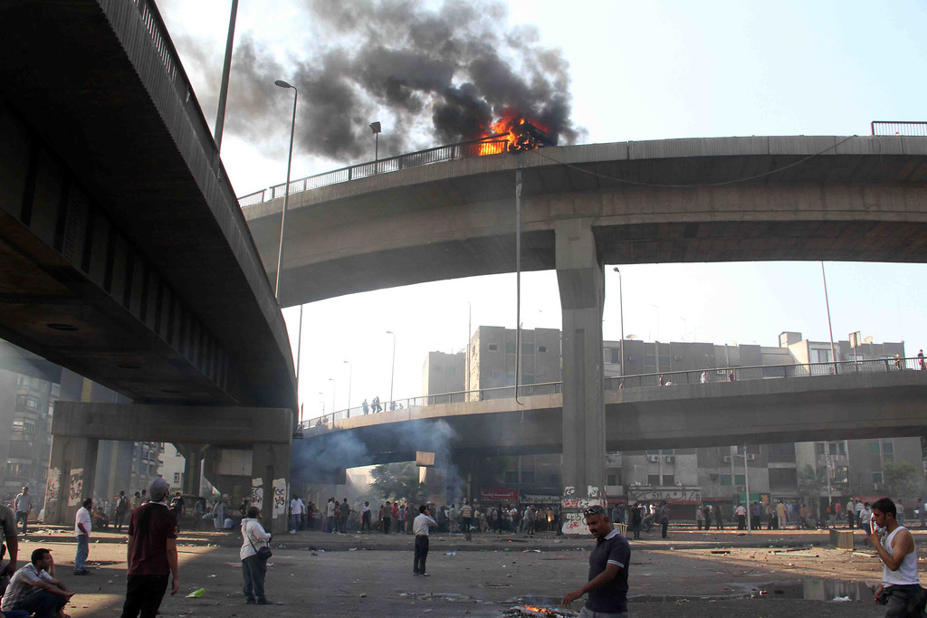 . Egyptian Muslim brotherhood supporters of Egypt\'s ousted president Mohamed Morsi look up at a vehicle burning on six October bridge during clashes with riot police after security forces dispersed Morsi supporters on August 14, 2013 in Cairo.  AFP PHOTO / KHALED  KAMEL/AFP/Getty Images