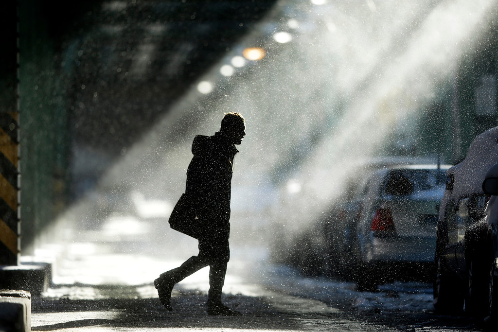 . The sun illuminates windblown snow as a man walks under elevated train tracks, Wednesday, Jan. 22, 2014, in Philadelphia.  A winter storm stretched from Kentucky to New England and hit hardest along the heavily populated Interstate 95 corridor between Philadelphia and Boston.   (AP Photo/Matt Rourke)