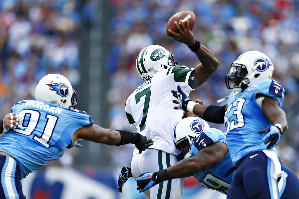 . NASHVILLE, TN - SEPTEMBER 29:  Geno Smith #7 of the New York Jets is hit while throwing a pass by Jurrell Casey #99 of the Tennessee Titans at LP Field on September 29, 2013 in Nashville, Tennessee.  (Photo by Wesley Hitt/Getty Images)