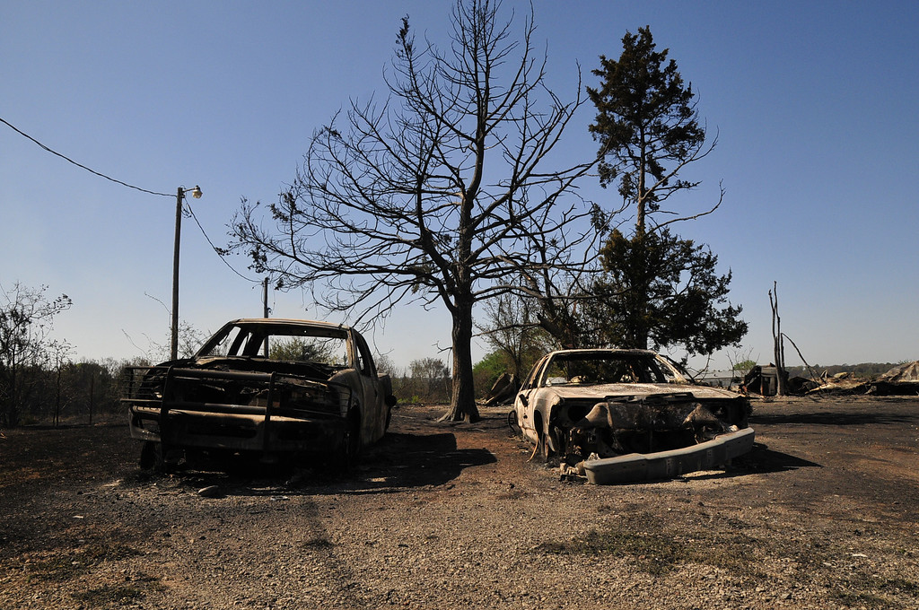 . The charred remains of two cars are left on Monday, May 5, 2014 in Guthrie, Okla., the day after a wildfire tore through the area. Firefighters worked through the night and into early Monday to battle the large wildfire that destroyed at least six homes and left at least one person dead after a controlled burn spread out of control in central Oklahoma.(AP Photo/Nick Oxford)