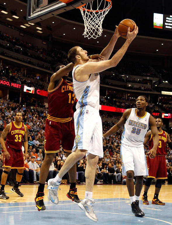 . Kosta Koufos #41 of the Denver Nuggets draws contact as he attempts a shot against Tristan Thompson #13 of the Cleveland Cavaliers at Pepsi Center on January 11, 2013 in Denver, Colorado. (Photo by Chris Chambers/Getty Images)