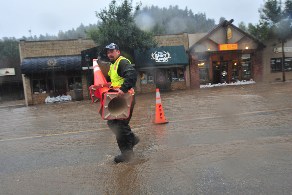 . Town employees place cones to narrow Elkhorn Avenue as water from the Big Thompson River overrun its banks. Officials are comparing the flood crest to that of the Big Thompson Canyon Flood of 1977.  Walt Hester/Estes Park Trail-Gazette
