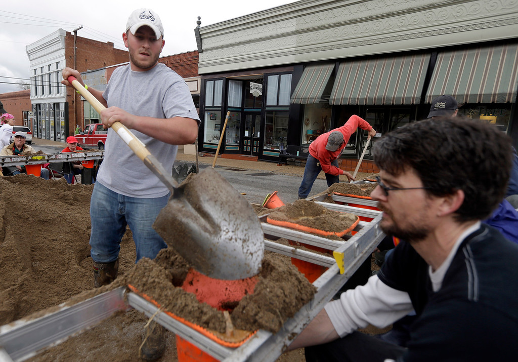 . Jimmy Stribling, left, and Chris Fitchett, right, along with other volunteers help to fill sand bags in hopes of holding back the rising Mississippi River Thursday, April 18, 2013, in Clarksville, Mo.  (AP Photo/Jeff Roberson)