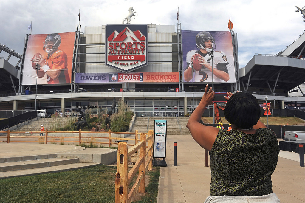 . Nicole Fields, of Denver,  takes a picture of the large banners of Denver Broncos quarterback Peyton Manning, left and Baltimore Ravens quarterback Joe Flacco, right,  hanging on the outside of Sports Authority Field at Mile High in Denver. Denver is hosting  the NFL season opener with the Denver Broncos taking on the Baltimore Ravens Thursday night.  Photo by Helen H. Richardson/The Denver Post