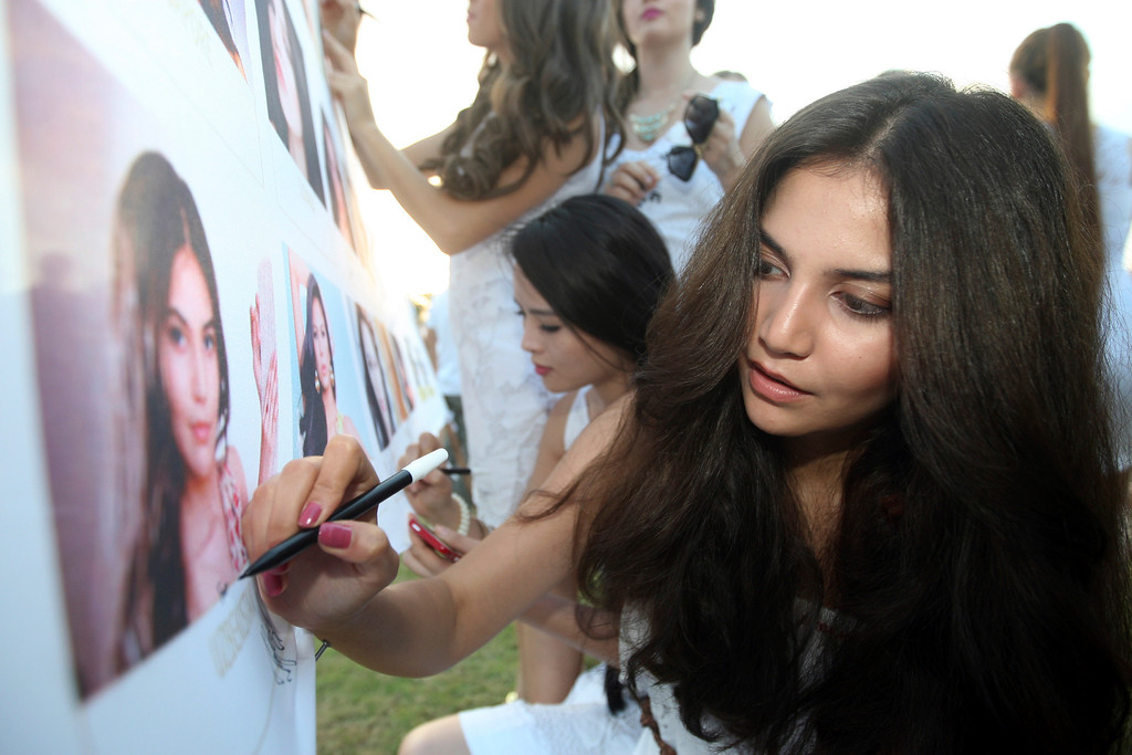 . Miss World contestant, Miss Uzbekistan Ganieva Rakhima, right, writes an autograph on her photo during the International World Peace Day celebrations at a park in Denpasar, Bali, Indonesia on Saturday, Sept. 21, 2013. The Miss World pageant final will be held in Bali on Sept. 28. (AP Photo/Firdia Lisnawati)