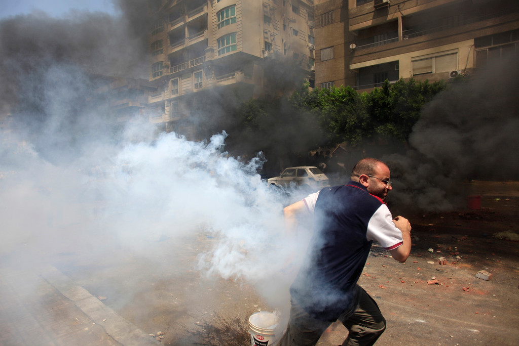 . Supporters of Egypt\'s ousted President Mohammed Morsi clash with the Egyptian security forces as security forces clear a sit-in by Morsi supporters in the eastern Nasr City district of Cairo, Egypt, Wednesday, Aug. 14, 2013.  (AP Photo/Khalil Hamra)