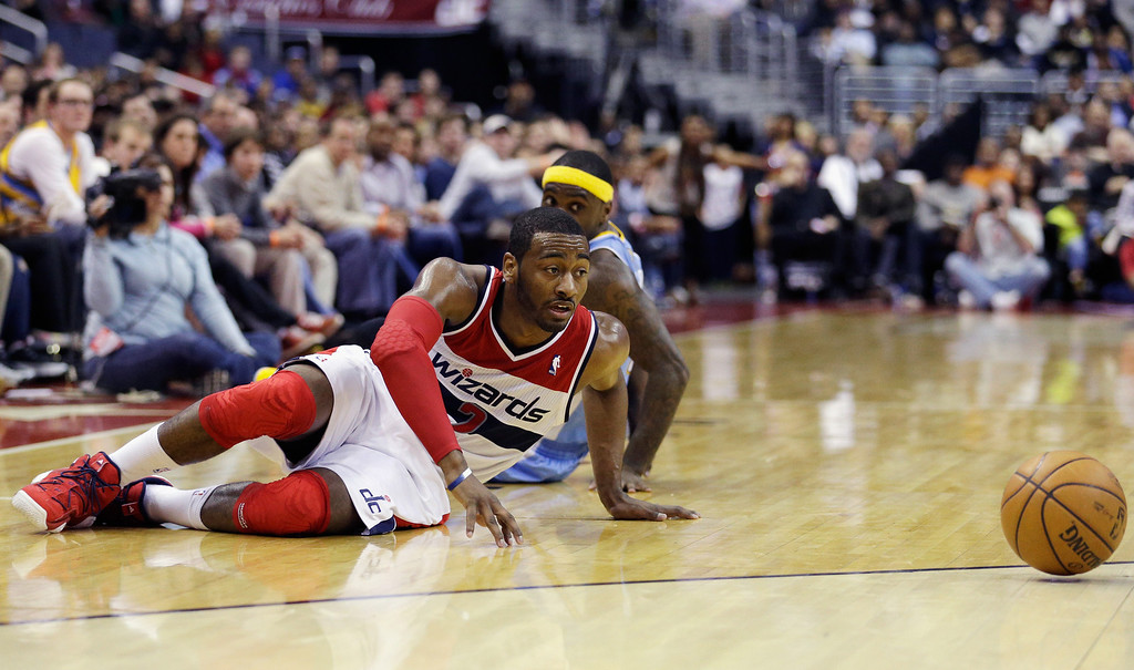 . WASHINGTON, DC - FEBRUARY 22: John Wall #2 of the Washington Wizards and Ty Lawson #3 of the Denver Nuggets go after a loose ball during the second half at Verizon Center on February 22, 2013 in Washington, DC.   (Photo by Rob Carr/Getty Images)