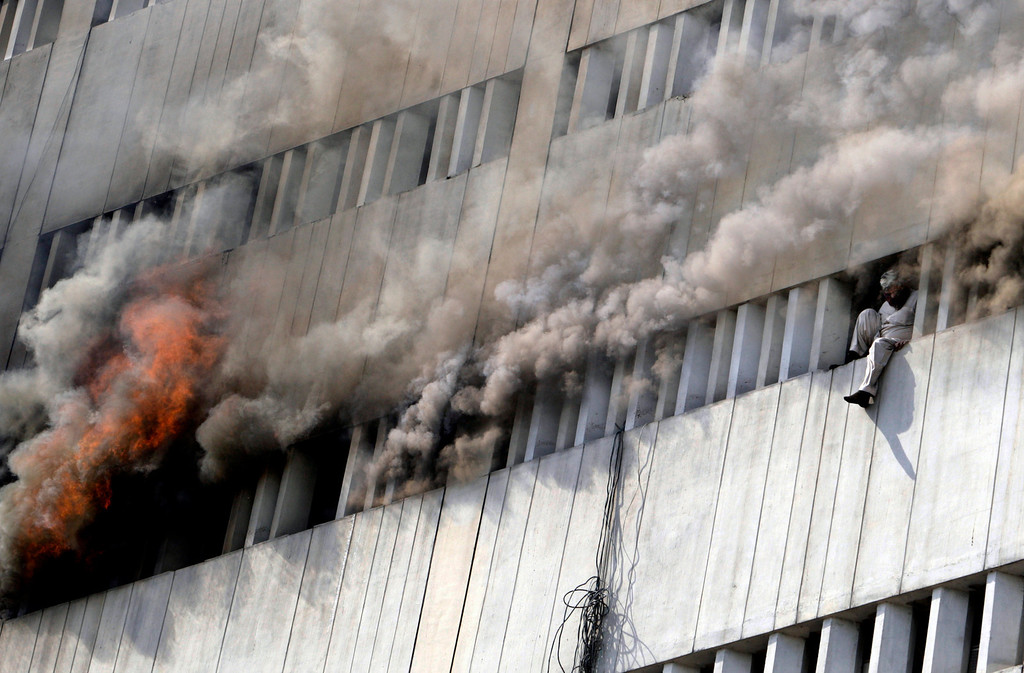 . A Pakistani man moments before jumping from the fifth floor of a building that caught on fire in Lahore, Pakistan, Thursday, May 9, 2013. The 13-story government building caught fire and quickly intensified spreading to three floors of the tall building. (AP Photo/K.M. Chaudary)