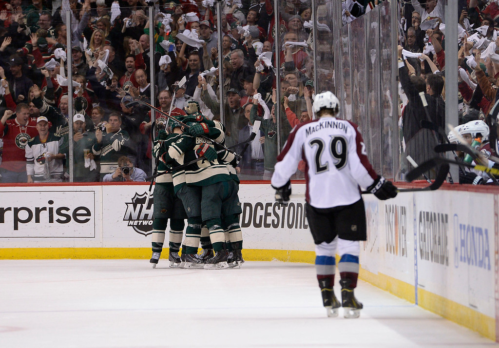 . Minnesota Wild celebrate Minnesota Wild left wing Zach Parise (11) game winning goal as Colorado Avalanche center Nathan MacKinnon (29) stands near the bench with his head down during the third period April 28, 2014 in Game 6 of the Stanley Cup Playoffs at Xcel Energy Center.  (Photo by John Leyba/The Denver Post)
