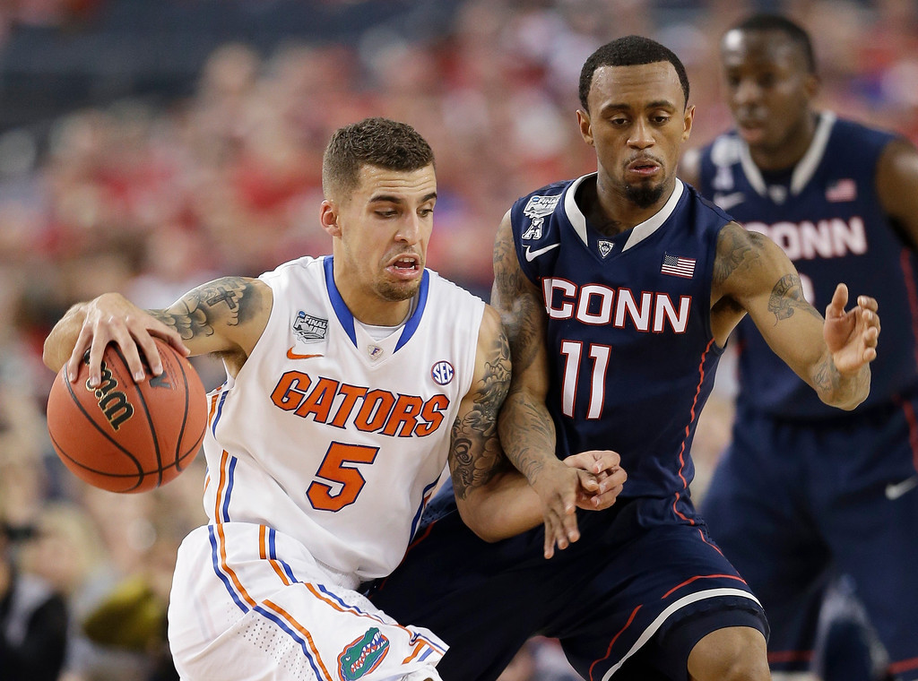 . Florida guard Scottie Wilbekin, left, drives past Connecticut guard Ryan Boatright during the first half of an NCAA Final Four tournament college basketball semifinal game Saturday, April 5, 2014, in Arlington, Texas. (AP Photo/David J. Phillip)