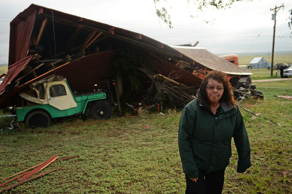 . Jennie Hoefler walks away after check out the damage to their barn that was destroyed in Hugo after a lager storm moved through town over night, June 5, 2014. The National Weather Service has sent a damage assessment team to the Hugo area to determine whether a tornado touched down after wind gusts of 111 mph were recorded overnight. (Photo by RJ Sangosti/The Denver Post)