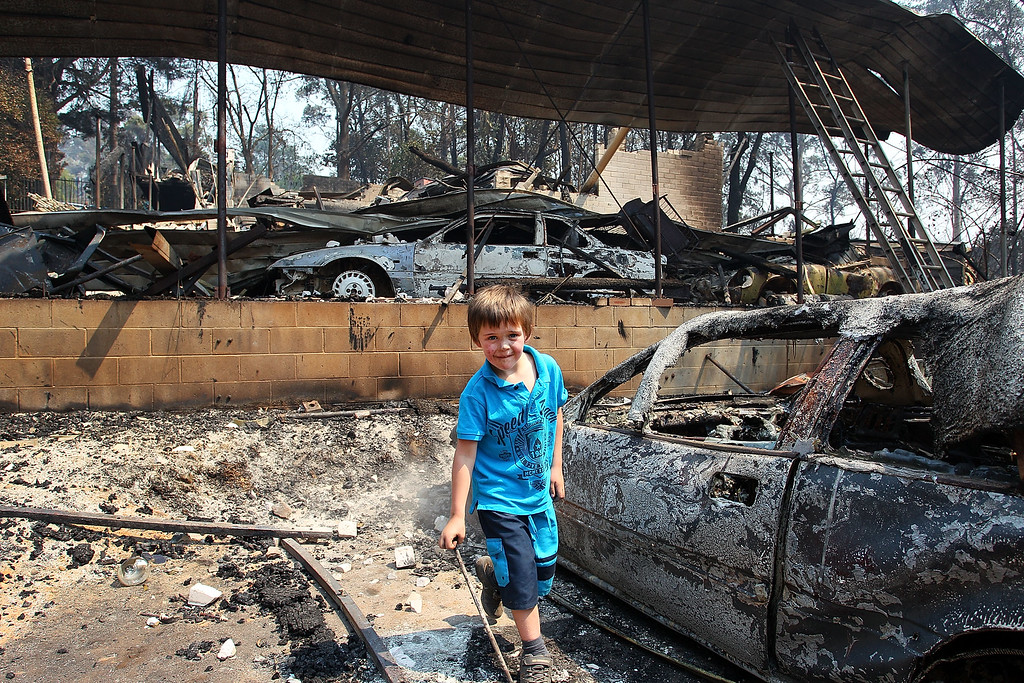 . Lyndon Dunlop inspects the remains of his grandparent\'s home of 41 years destroyed by bushfire on October 21, 2013 in Winmalee, Australia.  (Photo by Lisa Maree Williams/Getty Images)