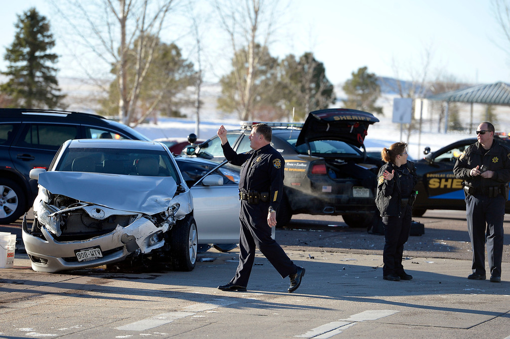 . Suspect in a car jacking starting in Longmont came to an end in Douglas County March 12, 2014 where he ran into several cars, jumping out and was apprehended behind a Wells Fargo Bank in a strip mall at Lincoln and Peoria.  (Photo by John Leyba/The Denver Post)