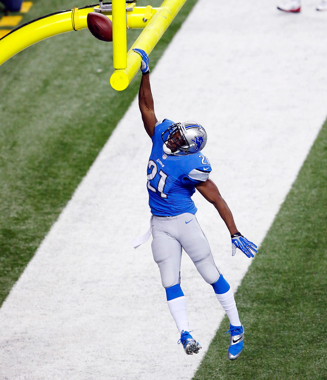 . Detroit Lions running back Reggie Bush (21) dunks the football on the goal post after his 14-yard touchdown run during the first quarter of an NFL football game against the Baltimore Ravens in Detroit, Monday, Dec. 16, 2013. (AP Photo/Paul Sancya)