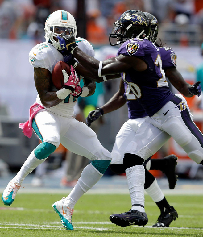 . Baltimore Ravens free safety Matt Elam, right, grabs Miami Dolphins wide receiver Mike Wallace by his face mask during the first half of an NFL football game, Sunday, Oct. 6, 2013, in Miami Gardens, Fla. (AP Photo/Wilfredo Lee)
