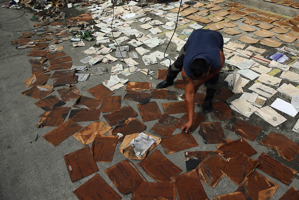 . An employee of an electrical retailer lays out customer documents to dry in the sun in preparations to re-opening in Taclaban on November 21, 2013 in Leyte, Philippines.  (Photo by Dan Kitwood/Getty Images)