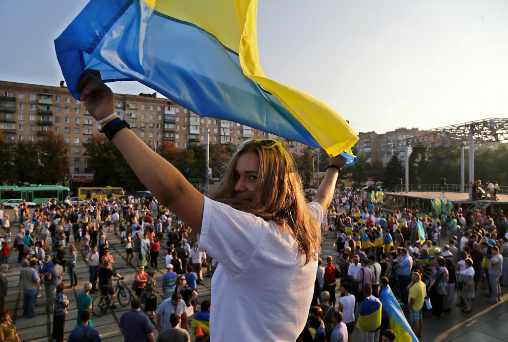 """. A girl waves with an Ukrainian flag during an anti-war meeting in the town of Mariupol, eastern Ukraine, Thursday, Aug. 28, 2014. Ukraine\'s president Petro Poroshenko called an emergency meeting of the nation\'s security council and canceled a foreign trip Thursday, declaring that \""""Russian forces have entered Ukraine,\"""" as concerns grew about the opening of a new front in the conflict. (AP Photo/Sergei Grits)"""