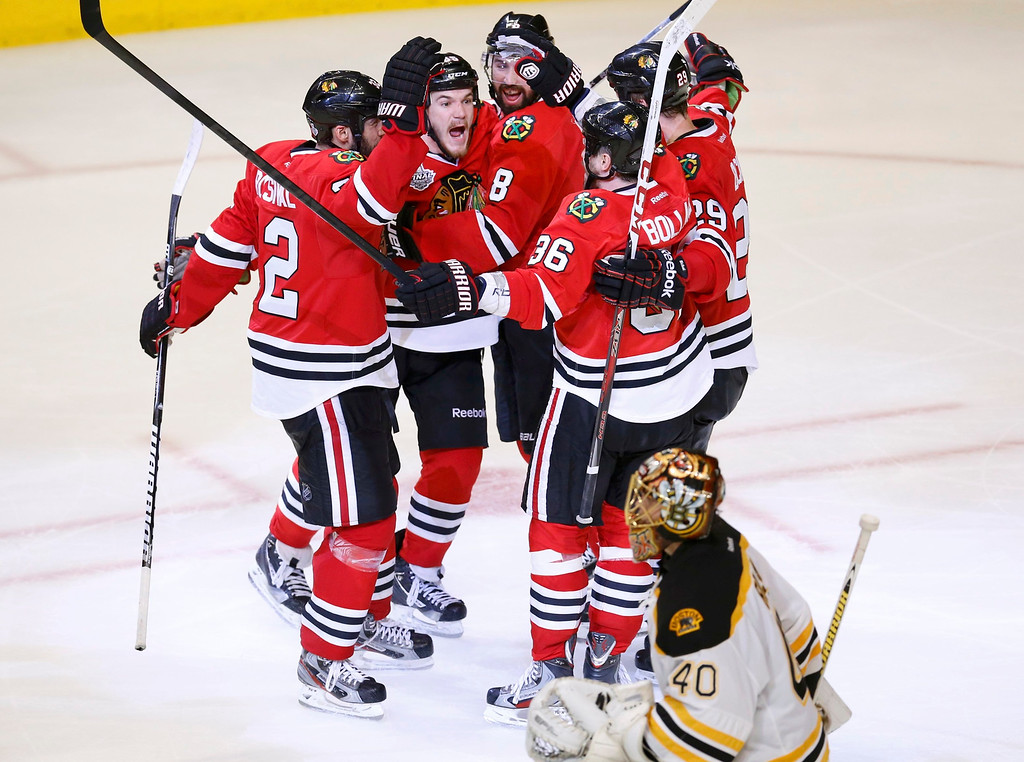 . Boston Bruins goalie Tuukka Rask (40) skates away as Chicago Blackhawks\' Andrew Shaw (C) celebrates his game-winning goal with teammates during triple overtime in Game 1 of their NHL Stanley Cup Finals hockey game in Chicago, Illinois, June 13, 2013.  REUTERS/Jim Young