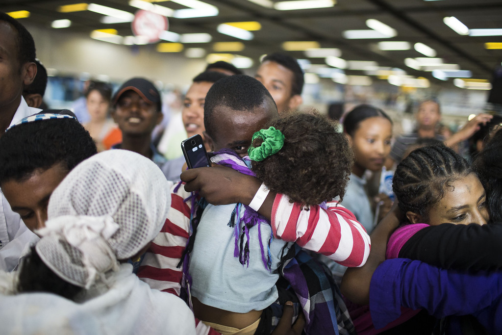 . TEL AVIV, ISRAEL - AUGUST 28:  New Jewish immigrants meet relatives during a welcoming ceremony after arriving on a flight from Ethiopia, August 28, 2013 at Ben Gurion airport near Tel Aviv, Israel. Over 400 Ethiopian Jews arrived on the flight to Tel Aviv, the last of a series of monthly flights that were part of Operation Dove\'s Wings, an Israeli government initiative to bring to Israel the remainder of the Falash Mura, members of the Ethiopian Jewish community whose ancestors converted to Christianity during the 19th and 20th century.  (Photo by Ilia Yefimovich/Getty Images)