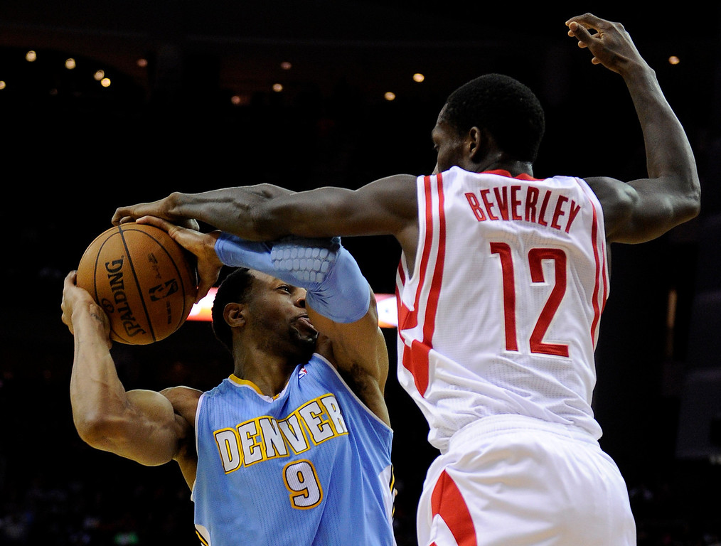 . Houston Rockets\' Patrick Beverley (12) tries to knock the ball away from Denver Nuggets\' Andre Iguodala (9) in the first half of an NBA basketball game Wednesday, Jan. 23, 2013, in Houston. (AP Photo/Pat Sullivan)