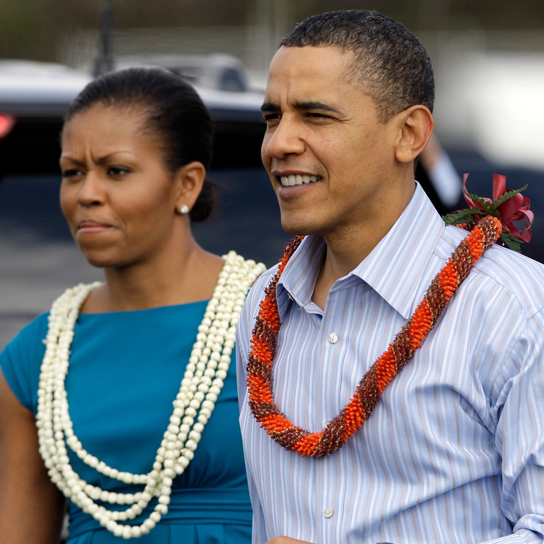 . President Barack Obama and first lady Michelle Obama, both wearing a leis, walk over to the crowd at Hickam Air Force Base in Honolulu Thursday, Dec. 24, 2009. They were in Hawaii for the holidays.  (AP Photo/Alex Brandon)