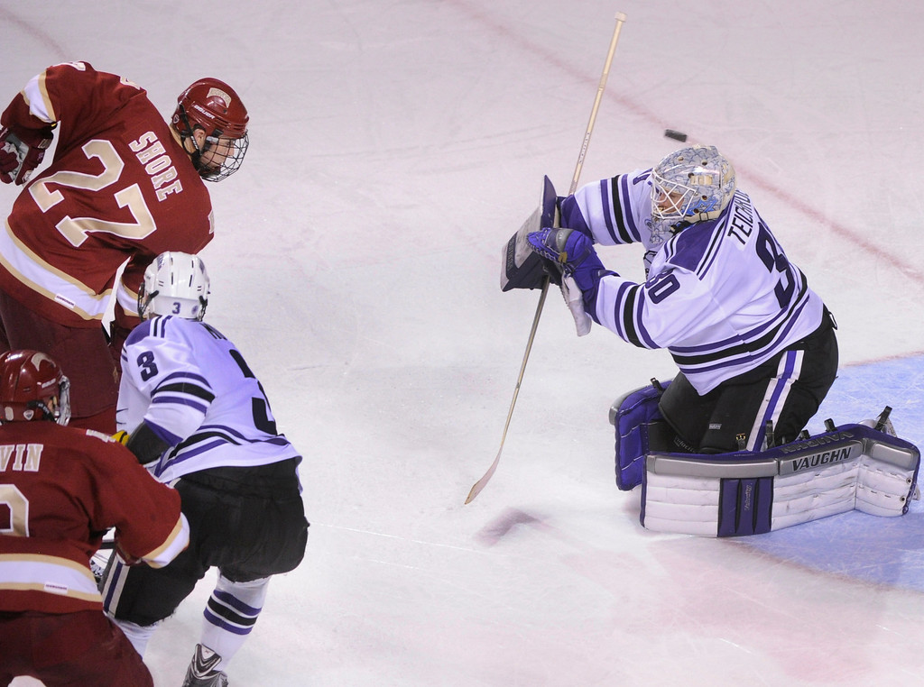 . DENVER, CO. - OCTOBER 25: Denver center Quentin Shore (27) lifted a shot over the head of Niagara goaltender Jackson Teichroeb (30) for a goal in the second period. The University of Denver hockey team hosted Niagara at Magness Arena Friday night, October 25, 2013. Photo By Karl Gehring/The Denver Post