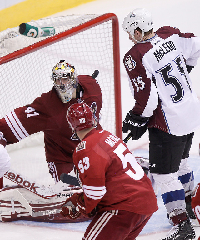 . Phoenix Coyotes goalie Mike Smith, top left, has a shot deflected off his mask as Colorado Avalanche left winger Cody McLeod, top right, and Coyotes defenseman Derek Morris, bottom, look for a rebound in the first period of NHL hockey game Saturday, April 6, 2013, in Glendale, Ariz. Smith earned a shout as the Coyotes won 4-0. (AP Photo/Paul Connors)