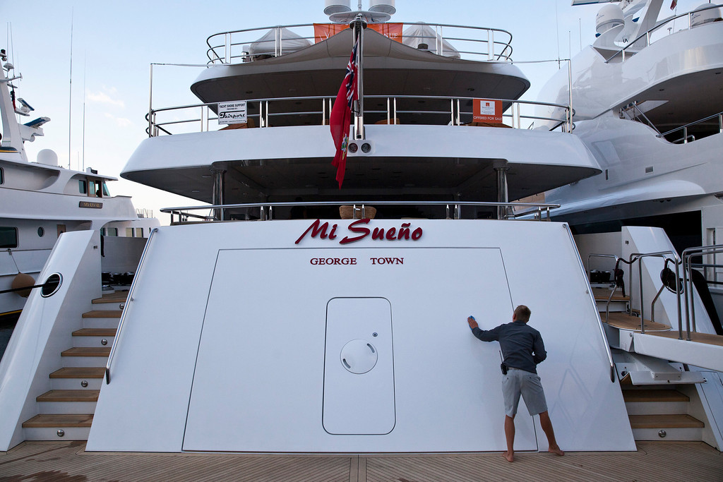 . A crew member cleans the stern of the 190ft (57.9m) motor yacht Mi Sueno, manufactured by Trinity Yachts LLC, as it sits moored in the harbor in Nice, France, on Wednesday, Sept. 25, 2013.  Photographer: Balint Porneczi/Bloomberg