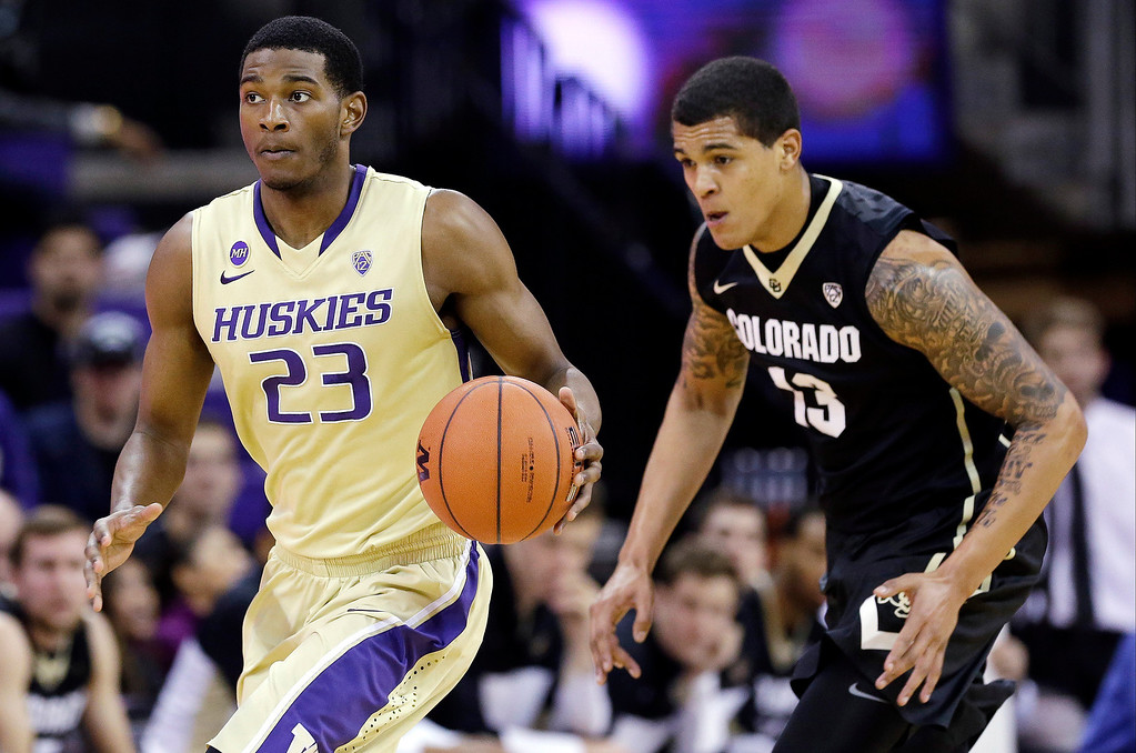 . Washington\'s C.J. Wilcox (23) drives in front of Colorado\'s Dustin Thomas in the second half of an NCAA college basketball game, Sunday, Jan. 12, 2014, in Seattle. Wilcox led all scorers with 31 points. Washington won 71-54. (AP Photo/Elaine Thompson)
