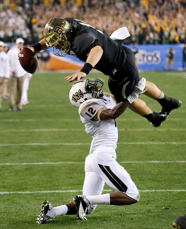 . Baylor quarterback Bryce Petty  leaps over Central Florida defensive back Jacoby Glenn (12) for a touchdown during the first half of the Fiesta Bowl NCAA college football game, Wednesday, Jan. 1, 2014, in Glendale, Ariz. (AP Photo/Ross D. Franklin)