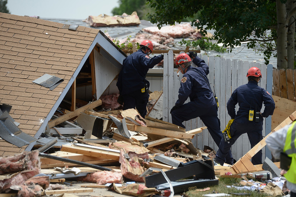 . Members of the North Area Tech Rescue Team, make their way through debris scattered from a house explosion on the 9300 block of Ingalls Street in Westminster, Colorado, Thursday afternoon June 13, 2013.  (Photo By Andy Cross/The Denver Post)