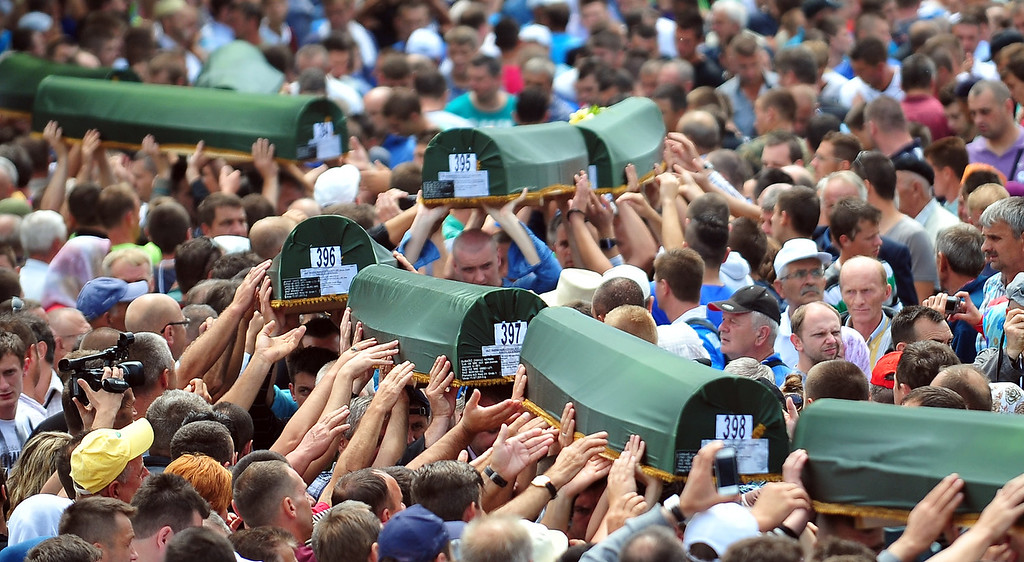 . Bosnian Muslims carry body caskets of their relatives killed during Srebrenica 1995 massacre as they prepare for mass burial at a memorial cemetery in the village of Potocari near the eastern Bosnian town of Srebrenica on July 11, 2013. Bosnia buried 409 victims of the Srebrenica massacre on July 11, including a newborn baby, on the 18th anniversary of the worst slaughter in post-war Europe. More than 15,000 people travelled to Potocari, near Srebrenica to attend the mass funeral of victims whose remains were found in mass graves and only identified almost two decades after the 1995 killing.  ELVIS BARUKCIC/AFP/Getty Images