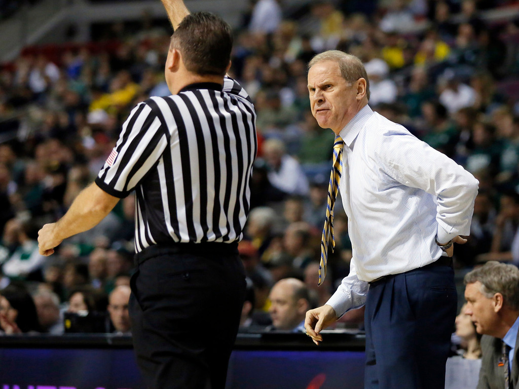 . Michigan head coach John Beilein, right, talks with an official in the first half of a third-round game of the NCAA college basketball tournament against Virginia Commonwealth, Saturday, March 23, 2013, in Auburn Hills, Mich. (AP Photo/Duane Burleson)