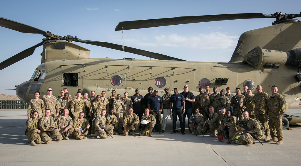 . (l-r in center of photo) Denver Broncos cornerback Champ Bailey, Tampa Bay Buccanneers guard Davin Joseph, Carolina Panthers wide receiver Steve Smith, Denver Broncos linebacker Von Miller, Cleveland Browns linebacker D�Qwell Jackson and Houston Texans defensive end J.J. Watt pose for a photo with troops stationed in the Middle East standing in front of a chinook helicopter during a stop on their week-long USO/NFL tour March 17, 2013. USO Photo by Fred Greaves