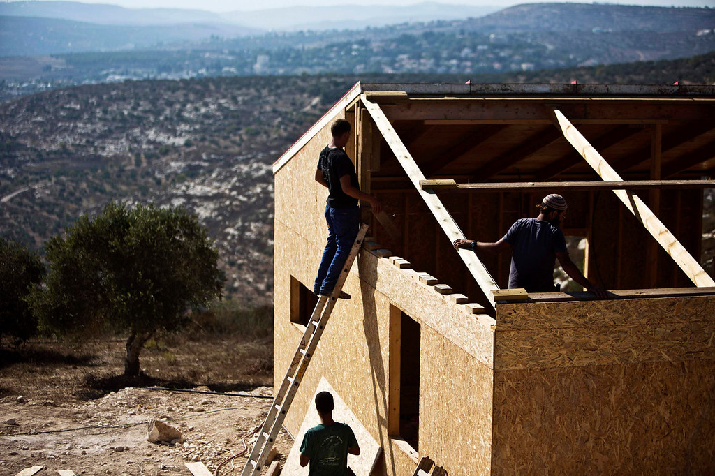 . Israelis work on the construction of a wooden house in the unauthorized Jewish settler outpost of Havat Gilad, south of the West Bank city of Nablus, July 25, 2013. An Israeli cabinet minister said on Thursday that U.S.-sponsored peace negotiations with the Palestinians could begin next week. Israel says new peacemaking would be without preconditions about the borders of a future Palestinian state in territories it occupied in the 1967 Middle East war. But the Palestinians say they want assurances about those borders first. REUTERS/Nir Elias