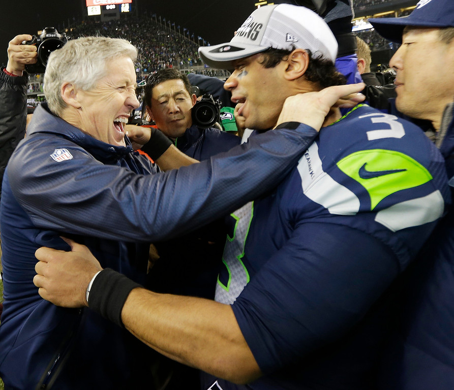 . Seattle Seahawks head coach Pete Carroll celebrates with Seattle Seahawks\' Russell Wilson after the second half of the NFL football NFC Championship game against the San Francisco 49ers Sunday, Jan. 19, 2014, in Seattle. The Seahawks won 23-17 to advance to Super Bowl XLVIII. (AP Photo/Ted S. Warren)