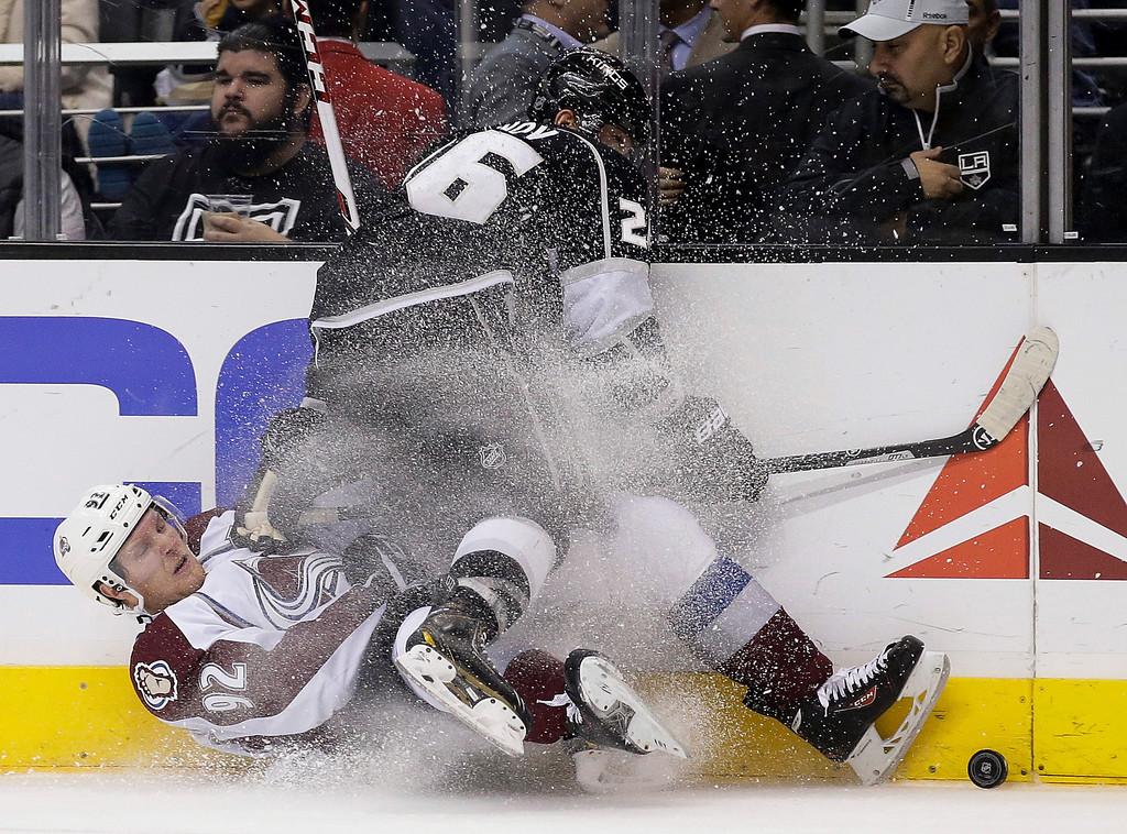 . Los Angeles Kings defenseman Slava Voynov, top, knocks Colorado Avalanche left wing Gabriel Landeskog to the ice during the first period of an NHL hockey game in Los Angeles, Saturday, Dec. 21, 2013. (AP Photo/Chris Carlson)