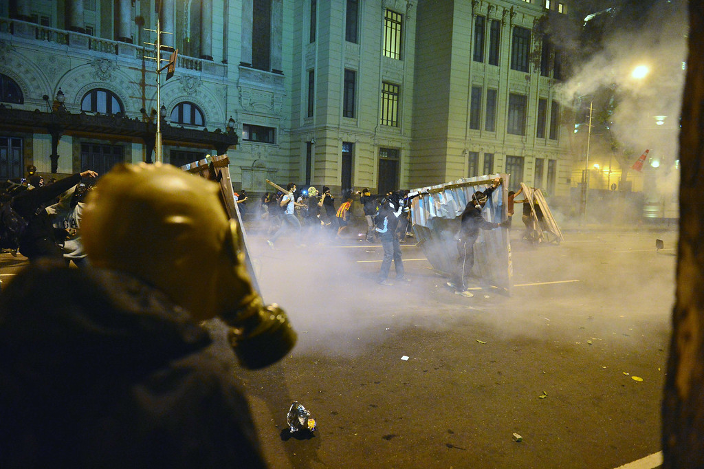 """. Demonstrators clash with the police during the \""""Teachers\' day\"""" protest in demand of better working conditions and against police violence, on October 15, 2013 in Rio de Janeiro, Brazil. AFP PHOTO / CHRISTOPHE SIMON/AFP/Getty Images"""