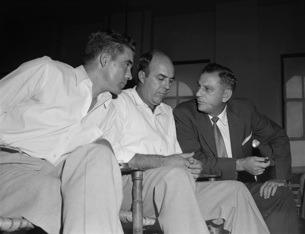""". Half-brothers Roy Bryant, left, and J.W. Milam, center, listen to their attorney, J.W. Kellum, as they sit in the courtroom, Sept. 23, 1955, in Sumner, Miss.,  prior to the opening of their first degree murder trial in Sumner.  The half-brothers are accused in the brutal murder of 14-year-old Chicago native, Emmett Till, who is black, for \""""wolf-whistling\"""" at Bryant\'s wife. (AP Photo)"""