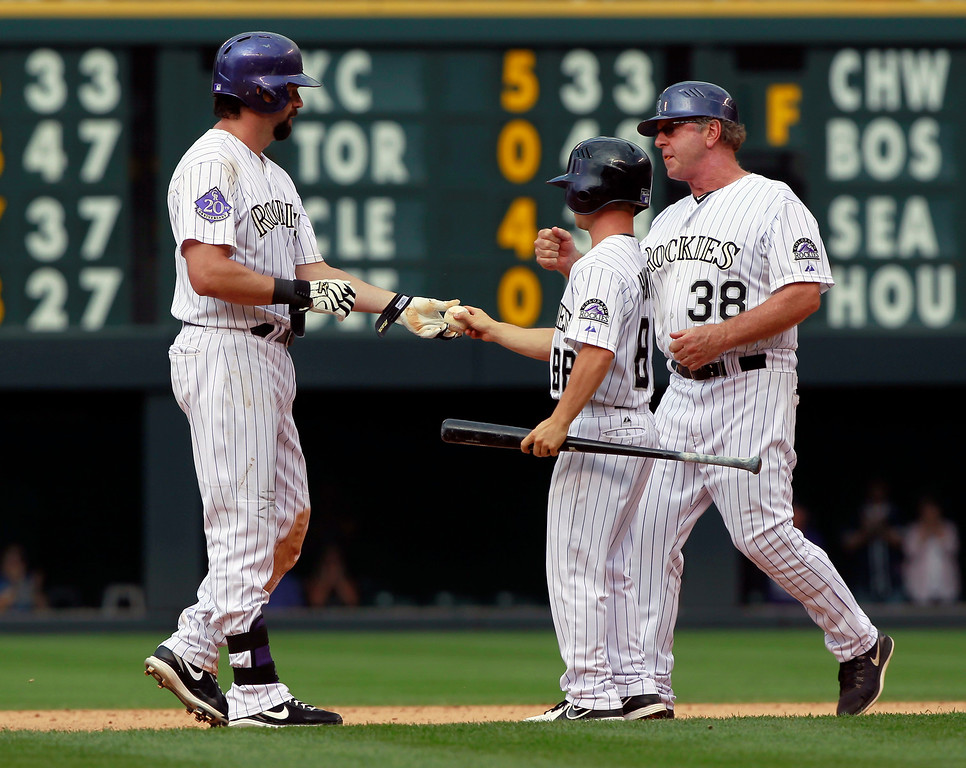 . Colorado Rockies\' Todd Helton, left, hands the ball to a batboy as first base coach Rene Lacheman, right, comes over to congratulate Helton after he hit a double for his 2,500th career hit against the Cincinnati Reds in the seventh inning of the Rockies\' 7-3 victory in a baseball game in Denver on Sunday, Sept. 1, 2013. (AP Photo/David Zalubowski)