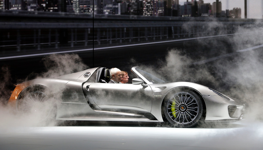 . Porsche CEO Matthias Mueller, left, and former rally driver Walter Roehrl arrive in the new Porsche 918 hybrid sports car during the first press day of the 65th Frankfurt Auto Show in Frankfurt, Germany, Tuesday, Sept. 10, 2013.  (AP Photo/Frank Augstein)