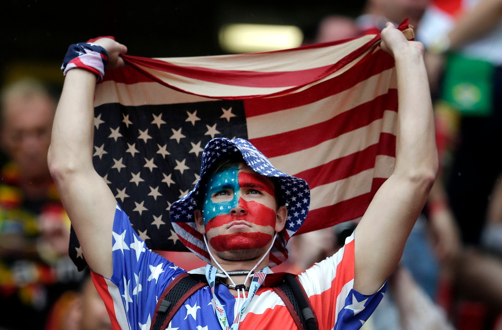 . A US fan holds a flag prior to the group G World Cup soccer match between the USA and Germany at the Arena Pernambuco in Recife, Brazil, Thursday, June 26, 2014. (AP Photo/Petr David Josek)