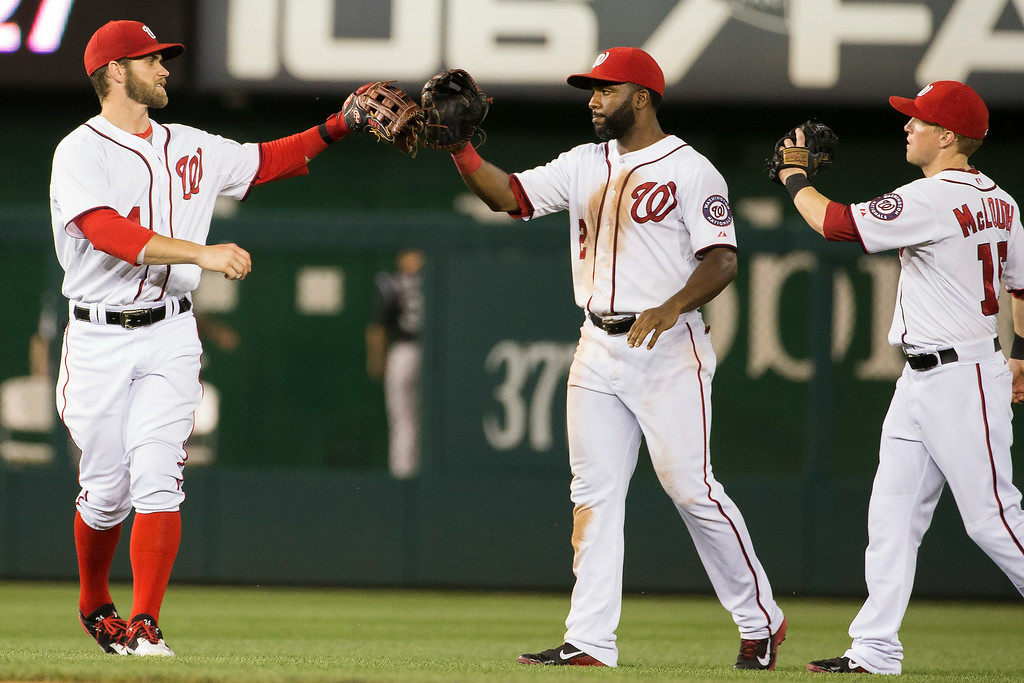 . Washington Nationals Bryce Harper, left, congratulates teammates Denard Span, center, and Nate McLouth after defeating the Colorado Rockies 7-1 at Nationals Park, on Tuesday, July 1, 2014, in Washington. (AP Photo/ Evan Vucci)
