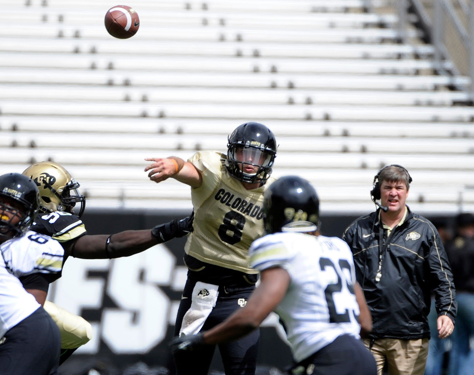 . BOULDER, CO.- APRIL13: Under the watchful eye of new head coach Mike MacIntyre, white QB Nick Hirschman goes back for a pass. The University of Colorado football team hosts its spring football game at Folsom Field under the direction of new head coach Mike MacIntyre. (Photo By Kathryn Scott Osler/The Denver Post)