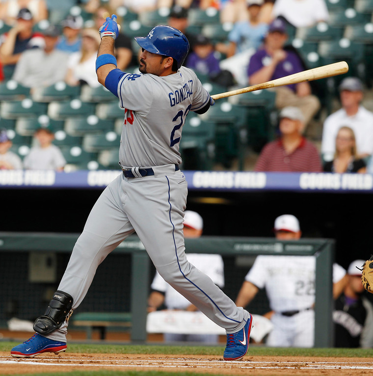 . Los Angeles Dodgers\' Adrian Gonzalez follows through on a single against the Colorado Rockies in the first inning of a baseball game in Denver on Thursday, July 4, 2013. (AP Photo/David Zalubowski)