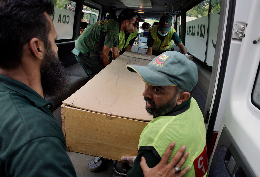 . Pakistani rescue workers unload the casket of a foreign tourist, who was killed by Islamic militants, from an ambulance to shift in a morgue of local hospital in Islamabad, Pakistan, Sunday, June 23, 2013.  (AP Photo/Anjum Naveed)