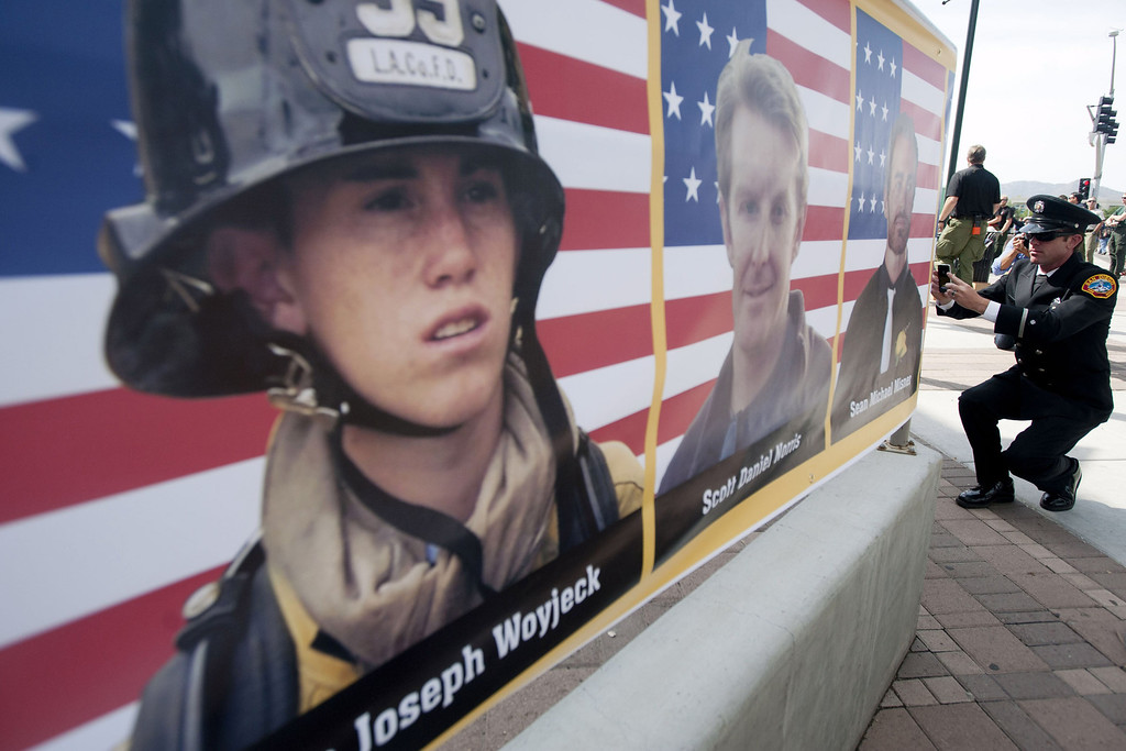 . Robert Bunsold with the San Diego fire department takes a picture of each of the 19 firefighters killed in a wildfire, at the entrance to a memorial service in their honor at Tim\'s Toyota Center July 9, 2013 in Prescott Valley, Arizona. (Photo by Laura Segall/Getty Images)
