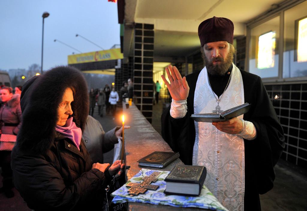 . An Orthodox priest prays outside the collapsed Maxima supermarket in Riga, Latvia, Friday, Nov. 22, 2013.  (AP Photo/ Roman Koksarov)