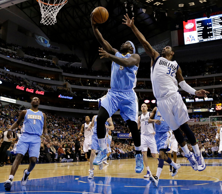 . Denver Nuggets small forward Jordan Hamilton, left, watches as point guard Ty Lawson (3) goes up for a shot-attempt as Dallas Mavericks\' O.J. Mayo (32) defends in the first half of an NBA basketball game on Friday, Dec. 28, 2012, in Dallas. (AP Photo/Tony Gutierrez)